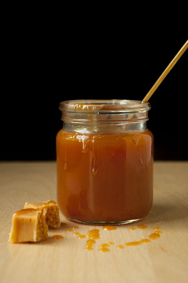 Ein Glas Karamellsauce mit Löffel und Toffees