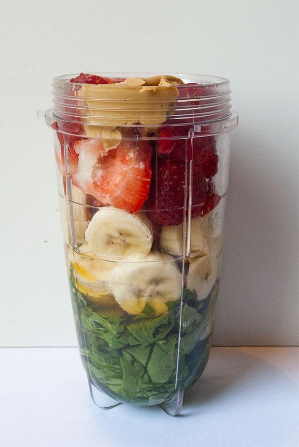 Grüner Smoothie aus Banane, Erdbeeren, Erdnussbutter und Spinat