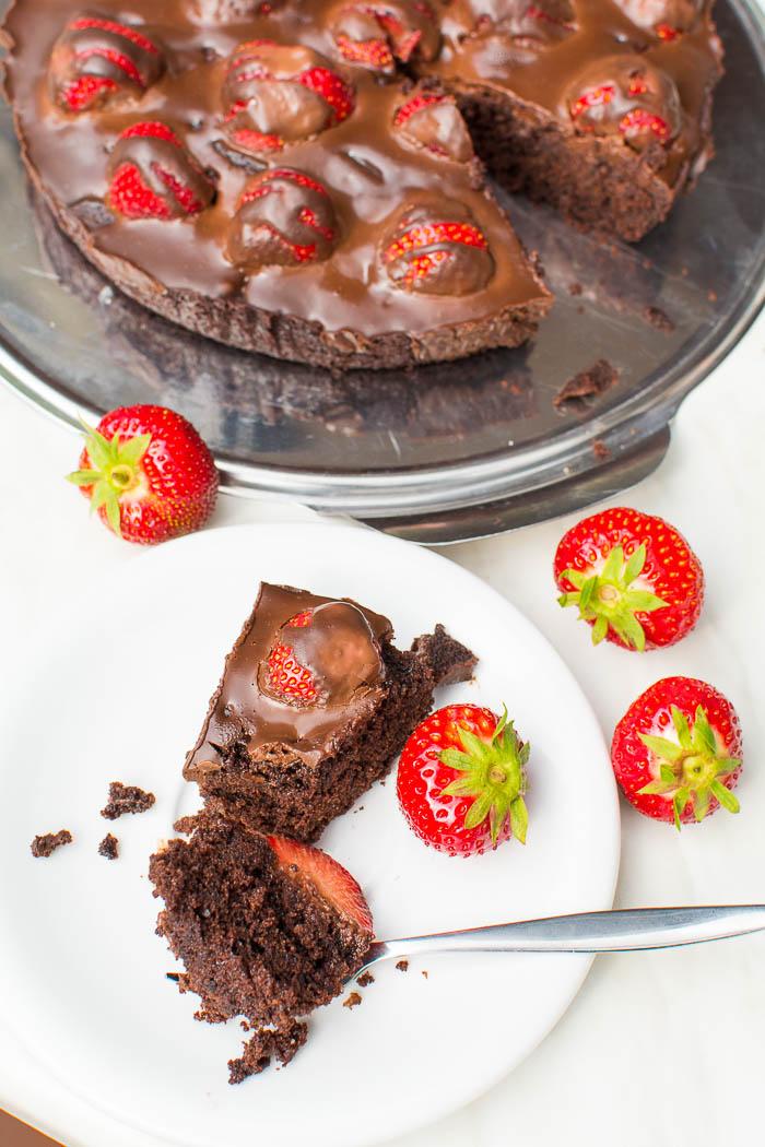 Ein Stück Brownie-Tarte mit frischen Erdbeeren und Ganache