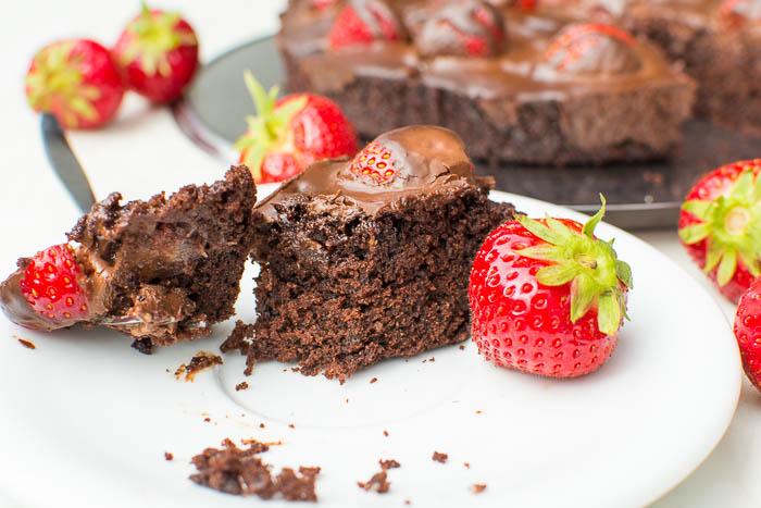 Nahaufnahme eines Stückes Brownie-Tarte mit frischen Erdbeeren und Ganache